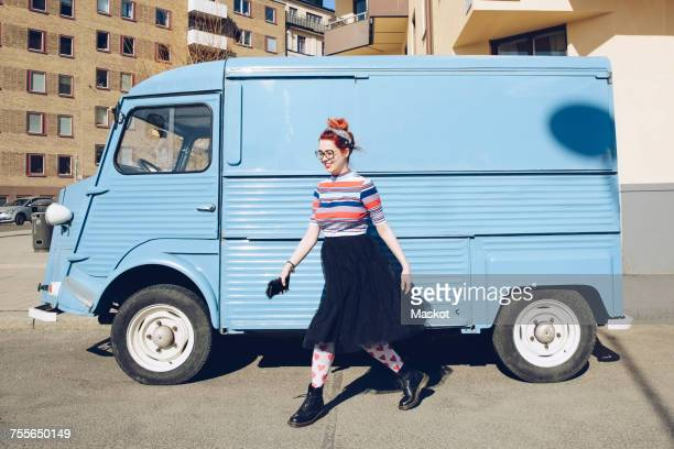 young woman walking by blue mini van on city street - white van stock photos and pictures