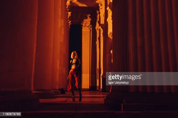 young woman walking by pillars at nigh - arch architectural feature stock pictures, royalty-free photos & images