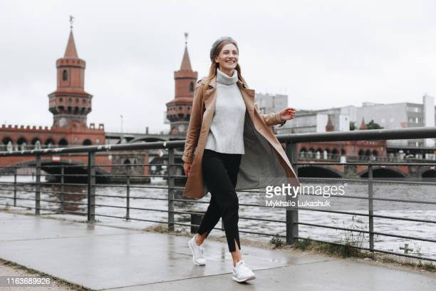 young woman walking by river in berlin, germany - walking stock-fotos und bilder