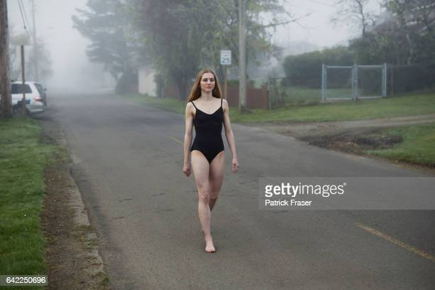 Young woman walking down a street in early morning mist wearing a leotard.