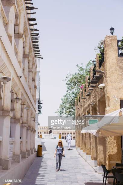 young woman walking down an alley in doha old town - down blouse stock-fotos und bilder