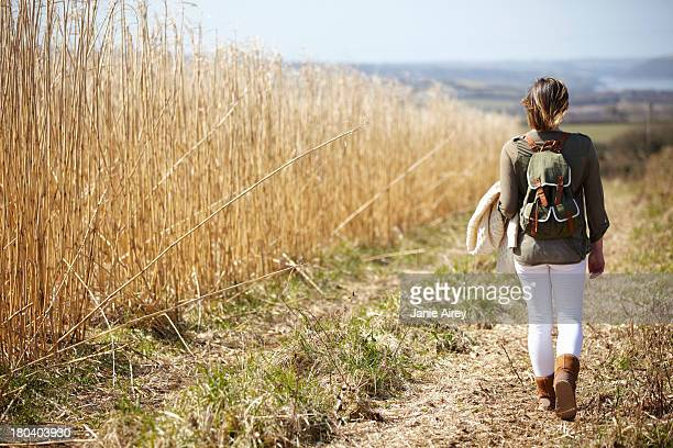 young woman walking down dirt track next to field of reeds - down blouse stock pictures, royalty-free photos & images