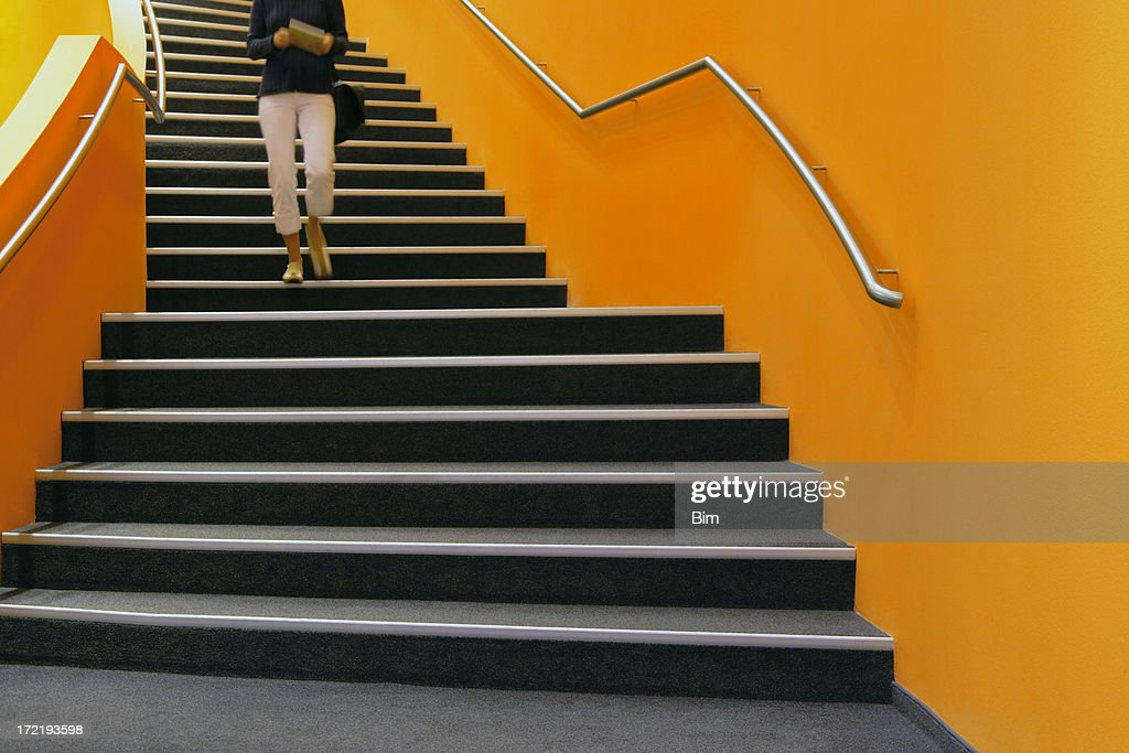 Young woman walking down orange stairs, reading book : Stock Photo