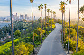 Young Woman Walking Down Palm Trees Street Revealing Downtown Los Angeles