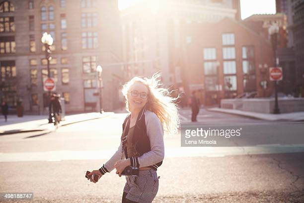 Young woman walking down street in Boston, carrying camera and smartphone