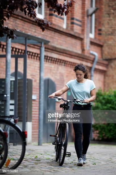 Young Woman Walking Down Street With Damaged Bicycle