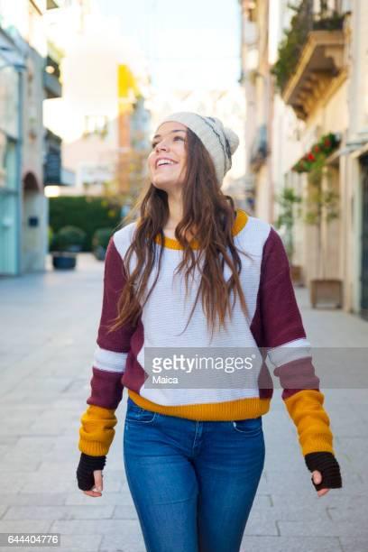 Jovem mulher a caminhar ao longo da rua