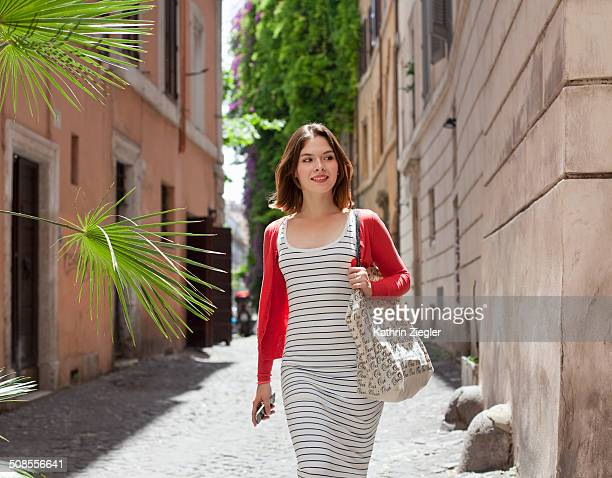 young woman walking down the street, rome, italy - shoulder bag stock pictures, royalty-free photos & images