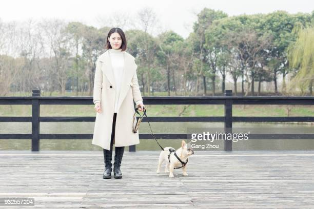 young woman walking her dog in park - chinese bulldog stock pictures, royalty-free photos & images