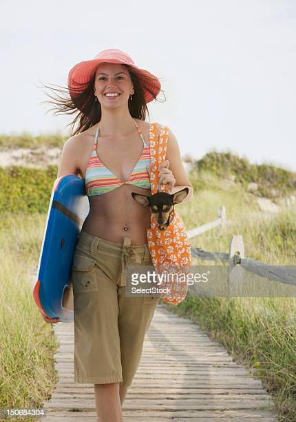 young woman walking holding small dog and boogie board - woman carrying tote bag stock photos and pictures