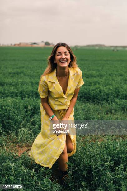 young woman walking in a green field - yellow dress stock pictures, royalty-free photos & images