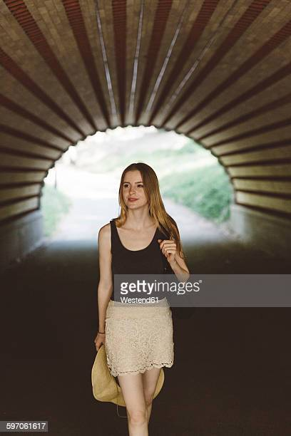 Young woman walking in a tunnel