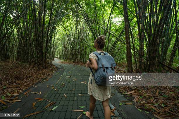 Young woman walking in bamboo forest- Bali, Indonesia