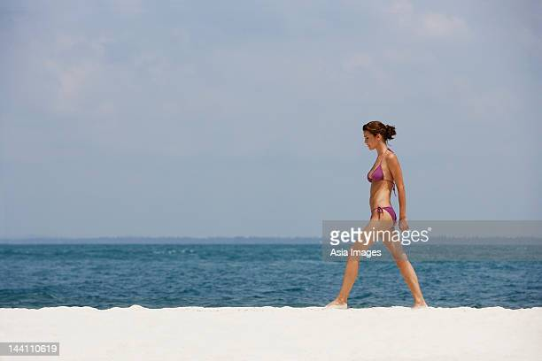 young woman walking in bathing suit on beach