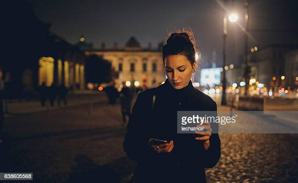 Young woman walking in Berlin at night checking phone