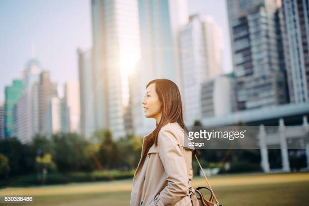 Young woman walking in city, against urban cityscape of Hong Kong