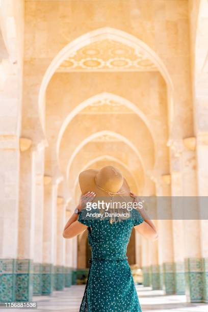 young woman walking in corridors of the hassan ii mosque. - casablanca stock pictures, royalty-free photos & images