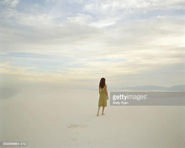 Young woman walking in desert, rear view