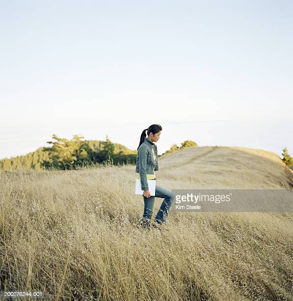 Young woman walking in field, carrying laptop computer, side view