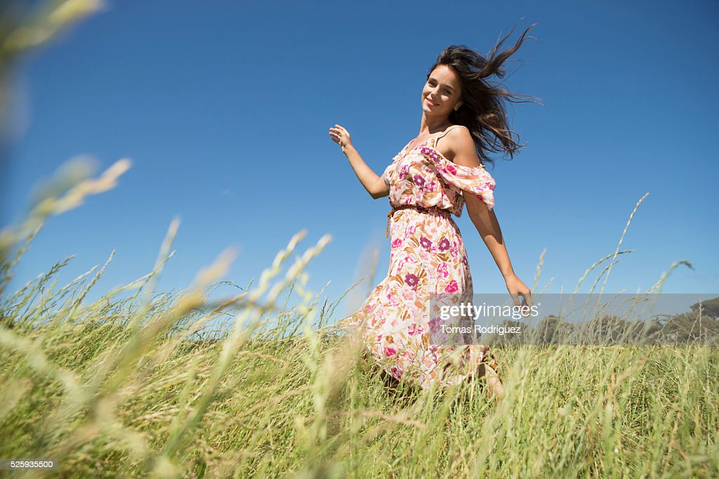 Young woman walking in field with arms raised : Stock Photo