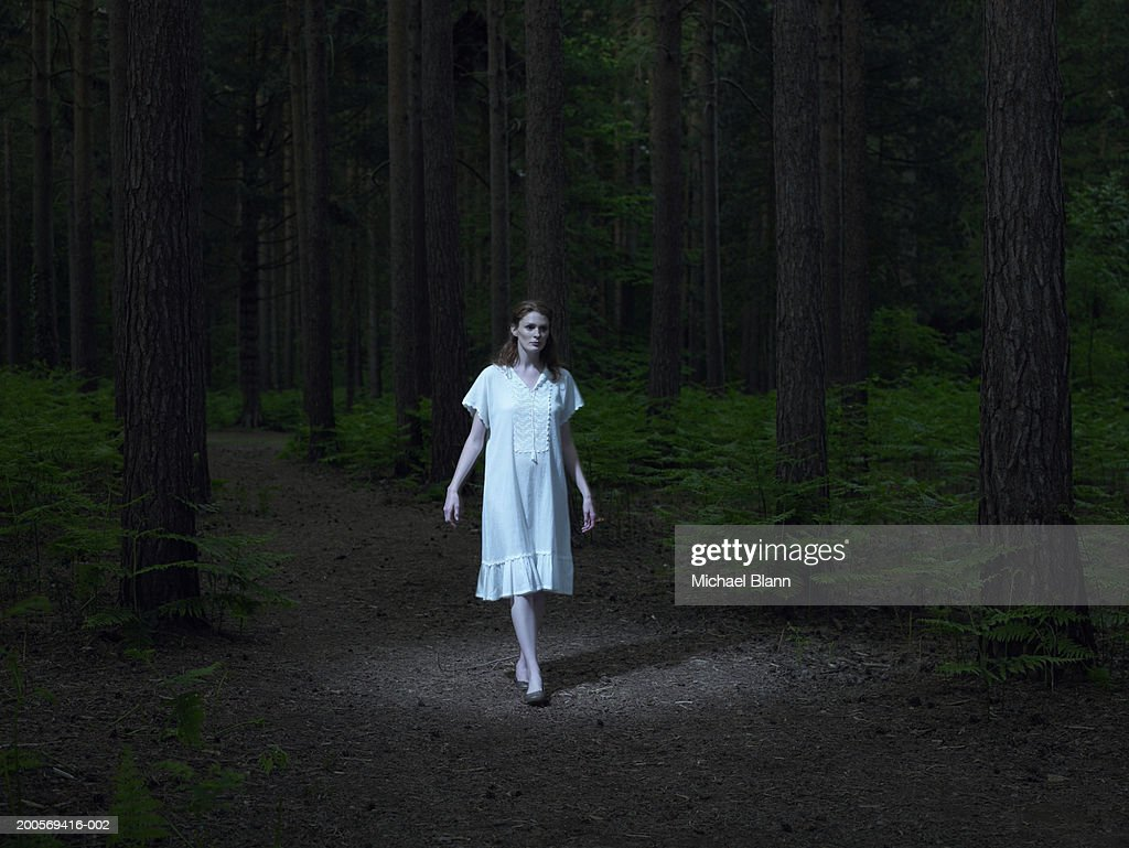 Young woman walking in forest : Stock Photo