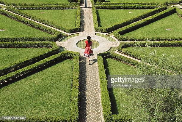 young woman walking in formal garden, elevated view - beslissingen stockfoto's en -beelden