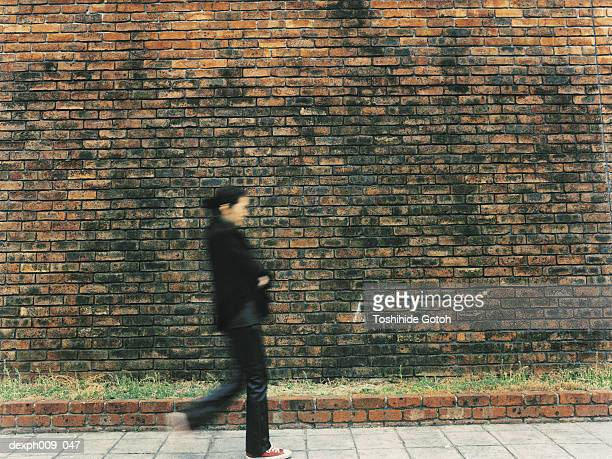 Young woman walking,  in front of Brick Wall