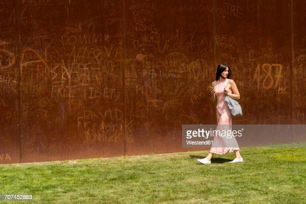 young woman walking in front of corten wall - shoulder bag stock pictures, royalty-free photos & images