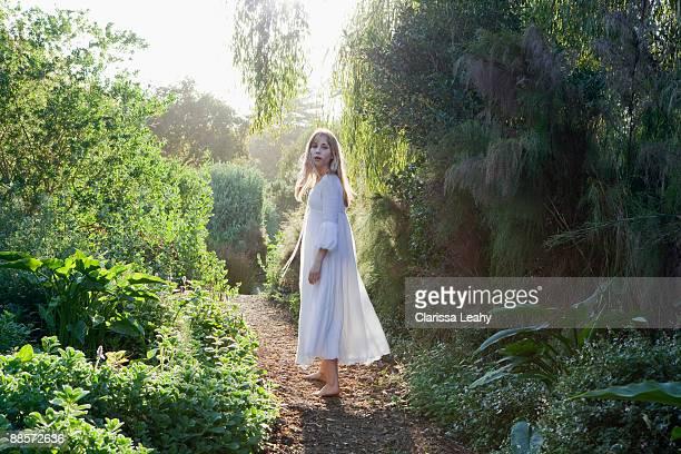 young woman walking in garden - alleen één tienermeisje stockfoto's en -beelden