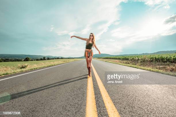 young woman walking in middle of road, leaving home, young woman running away, runaway, carefree woman, life balance - freie straße stock-fotos und bilder