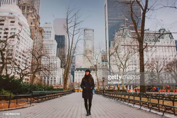 mulher nova que anda no parque central de nyc no inverno - central park manhattan - fotografias e filmes do acervo