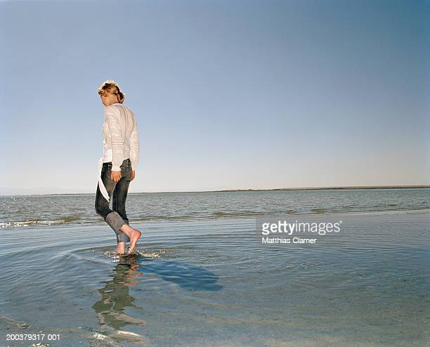 Young woman walking in ocean, side view
