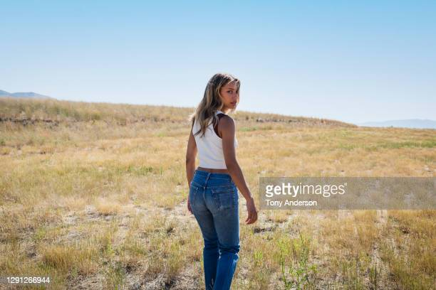 young woman walking in open field - black trousers stock pictures, royalty-free photos & images