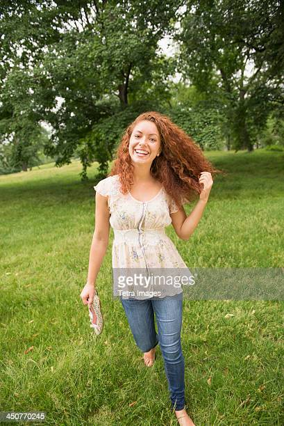 young woman walking in park - barefoot redhead stock photos and pictures