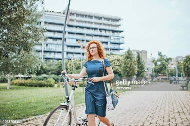 young woman walking in park, pushing bicycle - pedalantrieb stock-fotos und bilder