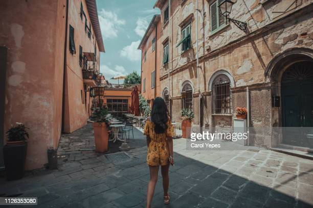 young woman walking in pisa street - pisa stock pictures, royalty-free photos & images