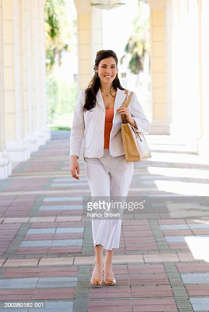 young woman walking in portico, portrait - white purse stock pictures, royalty-free photos & images