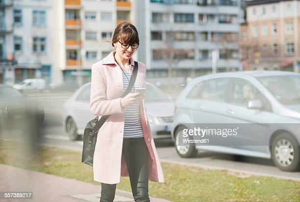 Young woman walking in street, using mobile phone