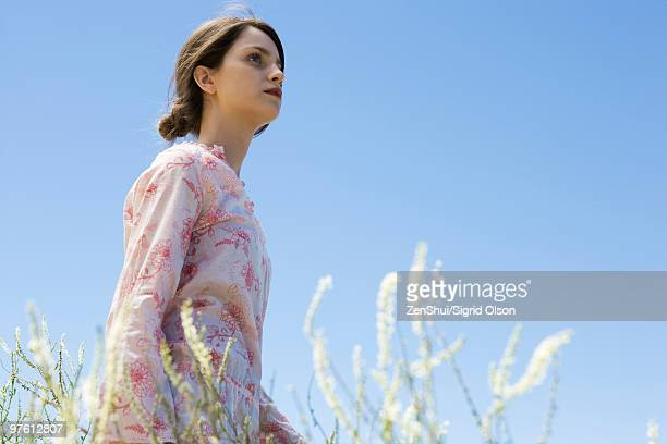 Young woman walking in tall grass, looking up
