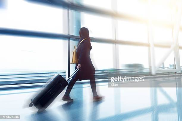 Young woman walking in the airport with luggage.