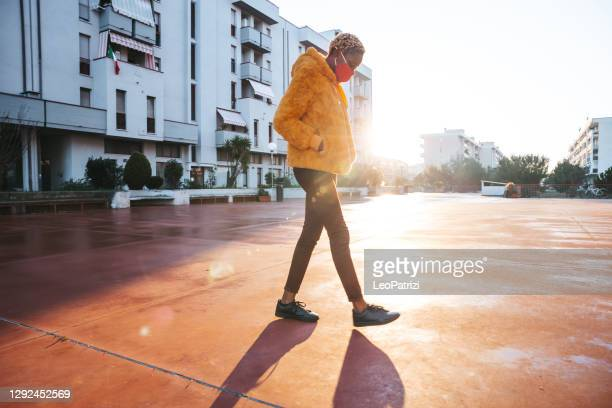 young woman walking in the neighborhood against the sunset - district stock pictures, royalty-free photos & images