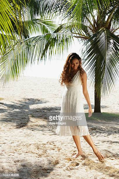 young woman walking in the sand with coconut trees in background