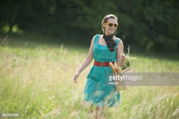 Junge Frau, die zu Fuß in die Sommerwiese