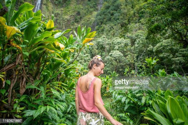 young woman walking in tropical rainforest exploring nature - water fall hawaii stock pictures, royalty-free photos & images