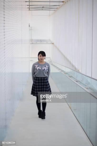 白い建物で歩く若い女性
