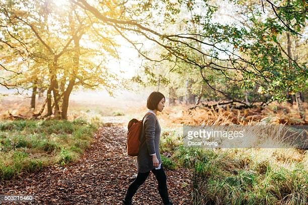 Young woman walking in woodland with yellow leaves in autumn