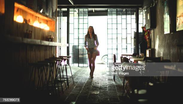 A young woman walking into a bar.