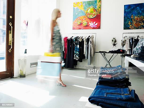 Young woman walking into clothing boutique