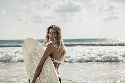 young woman walking into the sea, holding a surfboard - gettyimageskorea
