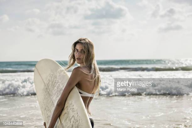 young woman walking into the sea, holding a surfboard